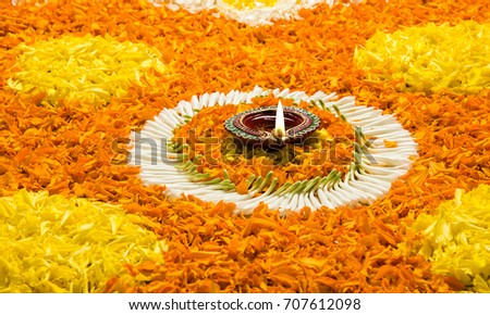 flower rangoli for Diwali or pongal or onam made using marigold or zendu flowers and red rose petals over white background with diwali diya in the middle, selective focus  #707612098
