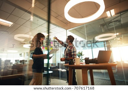 Young man and woman working together in office. Creative professionals working on new project.
