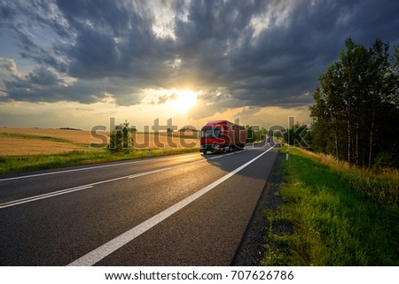 Red trucks arriving on the asphalt road along a field with golden grain in rural landscape at sunset with dark clouds #707626786