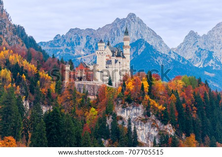 Beautiful autumn scenery of Neuschwanstein Castle with colorful autumn trees and the Alps on background. Bavaria, Germany. #707705515