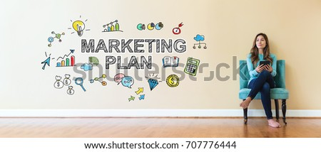 Marketing Plan text with young woman holding a tablet computer in a chair #707776444