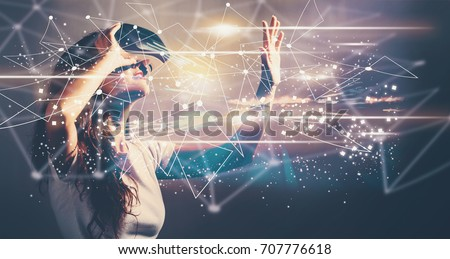 Links with young woman using a virtual reality headset Royalty-Free Stock Photo #707776618