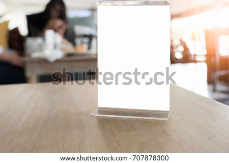 Mock up Menu frame in Bar restaurant ,Stand for booklets with white sheets of paper acrylic tent card on wooden table on.