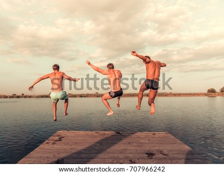 Handsome guys are jumping from pier into the lake, beautiful view #707966242