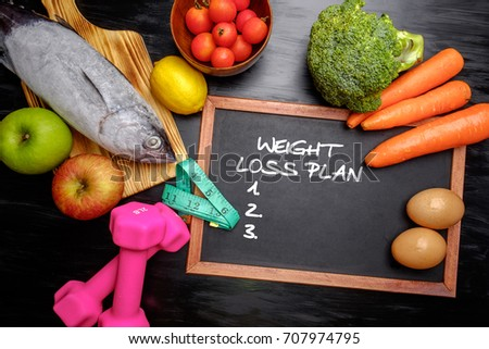 Weight loss plan on chalkboard, health conceptual. Healthy fresh low carbohydrates food; egg, fish, lemon, tomatoes, apple, carrot and broccoli with dumbbell and measur #707974795