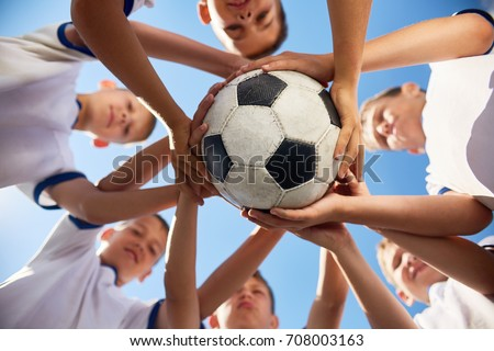 Low angle view of boys in junior football team standing in circle holding ball together against  blue sky, focus on ball Royalty-Free Stock Photo #708003163
