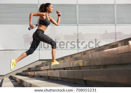 Athletic woman running up to the stone stairs with bottle of water in City  with fitness tracker #708055231