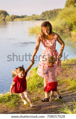 Mom with children twins on the river bank #708057028