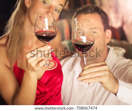 Couple tasting red wine in cellar at winetasting with glasses in their hands #708067474