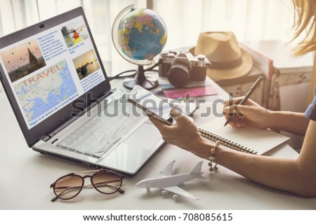 Young woman planning vacation trip and searching information or booking an hotel on a smart phone and laptop, Travel plan concept Royalty-Free Stock Photo #708085615