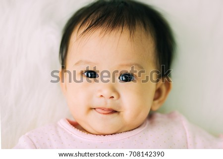 Happy and cute newborn baby lying on white blnket. Close up picture of smiling face.