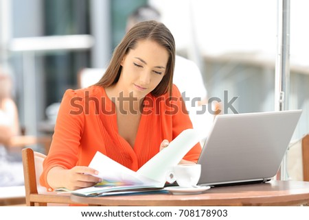 Single serious entrepreneur working reading documents sitting in a restaurant #708178903