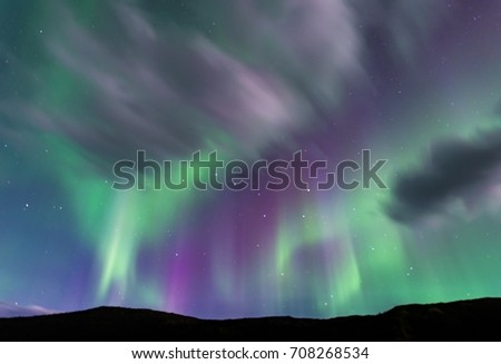 Green and purple Aurora borealis over silhouetted foreground; the Big Dipper shows prominently in the center #708268534