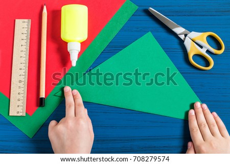 Making three-dimensional Christmas tree from paper to decorate room. Original children's art project. DIY concept. Step-by-step photo instructions. Step 2. Child makes triangle out of square Royalty-Free Stock Photo #708279574