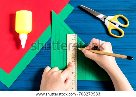 Making three-dimensional Christmas tree from paper to decorate room. Original children's art project. DIY concept. Step-by-step photo instructions. Step 3. Child makes markings, draws lines Royalty-Free Stock Photo #708279583