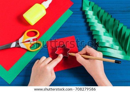 Making three-dimensional Christmas tree from paper to decorate room. Original children's art project. DIY concept. Step-by-step photo instructions. Step 8. Child draws star Royalty-Free Stock Photo #708279586