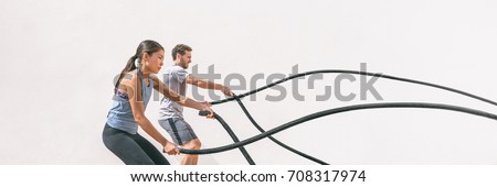 Gym fitness sport fit couple working out battle rope exercise banner panorama. Woman and man cross training arms muscles and cardio with battling rope. Core workout panoramic crop. #708317974