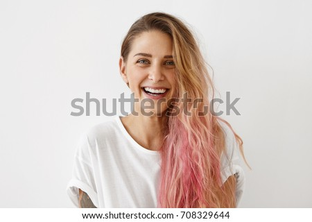 Picture of stylish trendy-looking young woman of European appearance wearing her messy pastel pink hair to the side smiling broadly, demonstrating her perfect white teeth. Youth and happiness