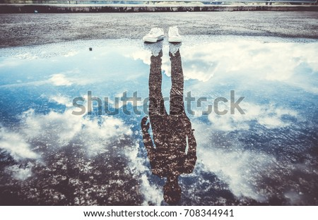 Reflection of man standing near puddle, Style is a reflection of your attitude and your personality,Education begins the gentleman, but reading, good company and reflection must finish him. Royalty-Free Stock Photo #708344941