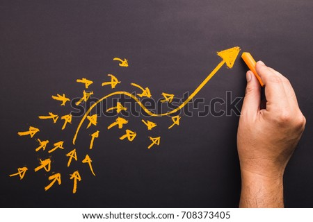 Hand draw a curve arrow leader with many small follower on chalkboard Royalty-Free Stock Photo #708373405