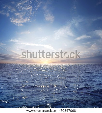 Rising sun on the horizon above a calm ocean or sea. On the blue sky white clouds #70847068