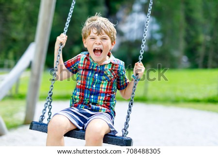 Funny kid boy having fun with chain swing on outdoor playground. child swinging on warm sunny summer day. Active leisure with kids. Happy crying boy #708488305