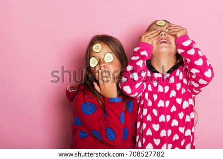 Kids pose on pink background. Childhood, friendship and happiness concept. Girls in colorful polka dotted pajamas send kisses and wear cucumber mask. Children with cheerful and loose hair