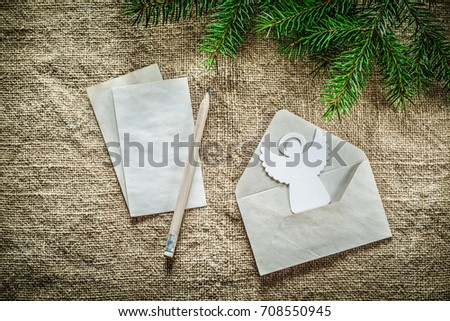 Pine tree branch envelope letter pencil angel on sacking background. #708550945