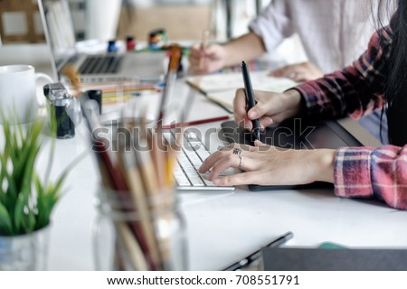 Young asian female designer using graphics tablet while working with computer at studio or office. Royalty-Free Stock Photo #708551791