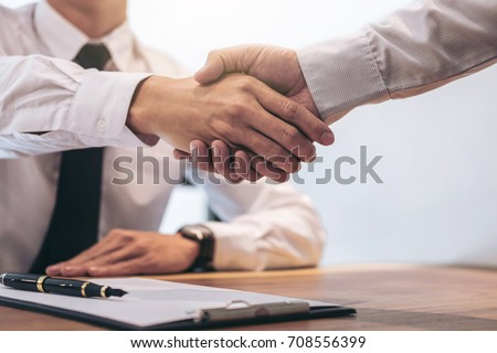 Real estate broker agent and customer shaking hands after signing contract documents for realty purchase, Bank employees congratulate, Concept mortgage loan approval. Royalty-Free Stock Photo #708556399