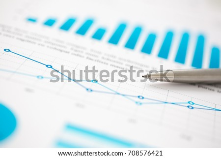 Financial statistics documents ball pen infographics at office table closeup. Internal Revenue Service inspector sum check, investigation, exchange market, earnings, savings, loan and credit concept #708576421