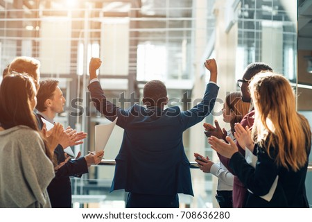 Business team celebrating a triumph with arms up Royalty-Free Stock Photo #708636280