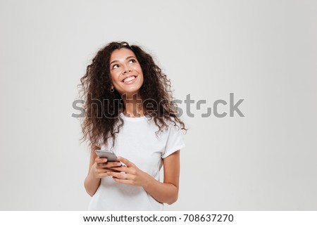 Smiling pensive woman holding smartphone in hands and looking up over gray background Royalty-Free Stock Photo #708637270