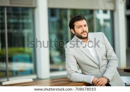 succesful man in white shirt standing next to an office building in a small break outside in a corporate area #708678010