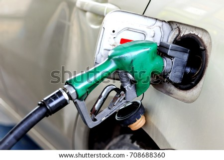 closeup car refueling on a petrol station white car with soft-focus and over light in the background #708688360