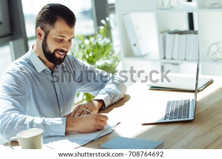 Charming young man making notes in the office #708764692