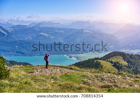 Young woman hiker with backpack enjoying panoramic view and looking ahead towards sun in mountains #708814354