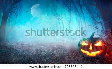 Halloween background. Spooky pumpkin with moon and dark forest. Halloween design with copyspace  Royalty-Free Stock Photo #708825442