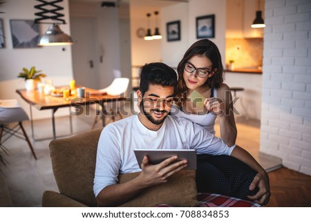 Photo of a young couple shopping online over digital tablet.