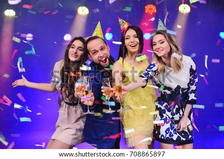 a guy and three girls rejoice and celebrate the party in the night club. Birthday, new year, corporate party, best friends #708865897