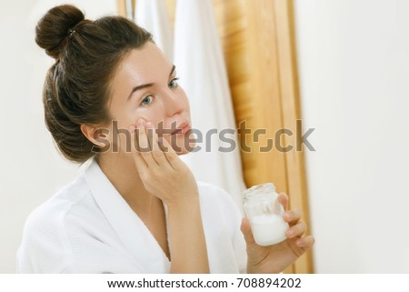 Woman is moisturizing her skin with a coconut oil #708894202
