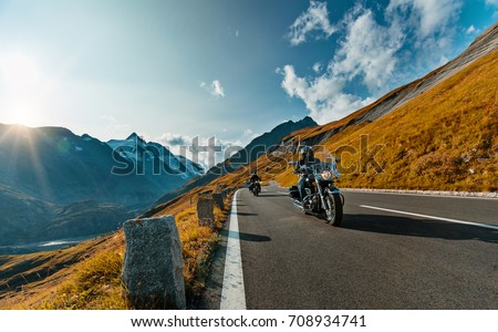 Motorcycle driver riding in Alpine highway on famous Hochalpenstrasse, Austria, central Europe. #708934741