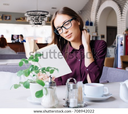 Concentrated at work. Confident young woman in smart casual wear working on laptop while sitting near window in creative office or cafe. #708942022