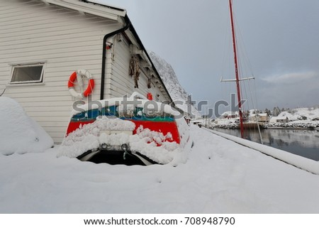 Small red-green fishing boats under heavy snowfall ashore alongside white wooden warehouses-pier deck on fishing port's west side-Festhaeltinden mounts. Hamnoy-Reine-Moskenes-Lofoten-Nordland-Norway. #708948790