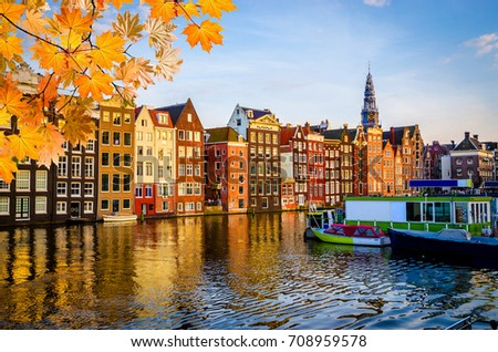 Traditional old buildings and boats in autumn at sunset in Amsterdam, Netherlands #708959578