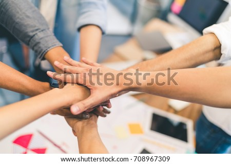 Business partners teamwork or friendship concept. Multi-ethnic diverse group of colleagues join hands together. Creative team, coworkers, or college students in project meeting at modern office Royalty-Free Stock Photo #708967309
