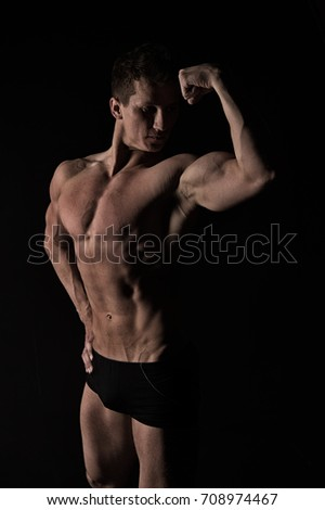 Athletic bodybuilder pose in pants. Man with muscular body. Sport and workout. man with bare chest. #708974467