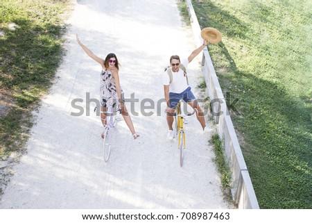 A spontaneous romantic tourist couple riding a bike on a cycle lane. Fashion blonde boyfriend and girlfriend walking on the park with vintage bike.. concept love Royalty-Free Stock Photo #708987463