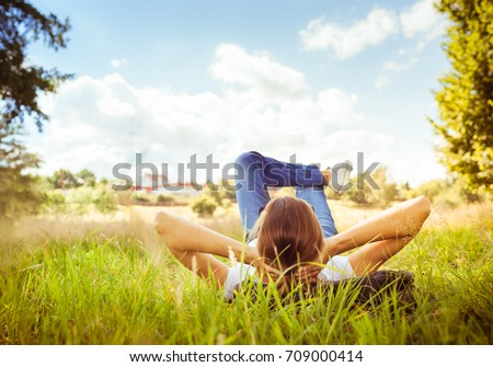 Young woman lying on grass looking up in the sky. People relaxing in outdoors.  #709000414
