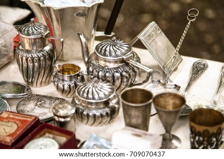 Antique silver teapots, creamer and other utensils at a flea market. Old metal tableware collectibles at a garage sale Royalty-Free Stock Photo #709070437